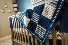 blue and silver baby blanket hanging over crib