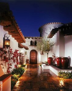 ~ Love the rotunda of this beautiful Spanish-style home.  Because most of this architecture has exterior white stucco, colorful flowers and vases add to make a warm and inviting ambience. ~