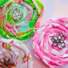 Rolled fabric flowers with rhinestone centers.... vintage button store, open your doors for me!
