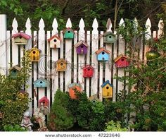birdhouses in pop colours on white picket fence by roji