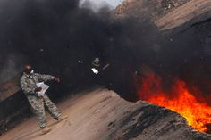 .In this undated file photo Master Sgt. Darryl Sterling tosses unserviceable uniform items into a burn pit at Balad Air Base, Iraq.