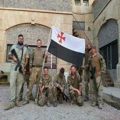 UK nationals embedded with the Peshmerga in Iraq to fight ISIS, most notably Timothy Scott (2nd from your right) and Steven Costa (holding the flag) pictured holding a Knights Templar flag (black, white and a red St. George's Cross). Knights Templar Flag, Bush Jr, Colorado College, George Cross, Military News, Pop Culture References, Confederate Flag, Islamic World, North Africa