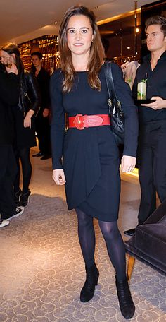 The socialite added a pop of color to her long sleeve black dress with a wide red belt for a book launch in London