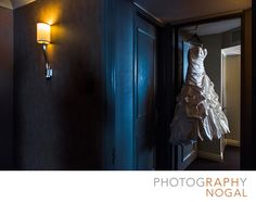 - Wedding Dress Hanging At The Doorway: For this photograph, I wanted to include the walls sconce as well as the dress to help balance the frame. The yellow from the lightbulb and the blue wall complement each other visually and as a colour palet.&nbsp,The natural light falling on the dress also hits it perfectly creating highlight and shadow areas on the dress making it appear more three dimensional.