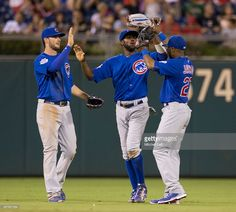 Kris Bryant #17, Dexter Fowler #24, and Austin Jackson #27 of the Chicago Cubs high five one another after the game against the Philadelphia Phillies on September 11, 2015 at Citizens Bank Park in Philadelphia, Pennsylvania. The Cubs defeated the Phillies 5-1.