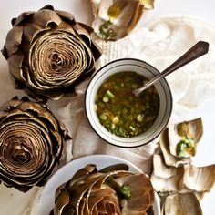 Artichokes with Scallion Vinaigrette   A generous portion of bay leaves in the steaming liquid here permeates the artichoke leaves and hearts with flavor and provides an enticing aroma as you serve the dish. The scallion vinaigrette balances the sweetness of the artichokes.