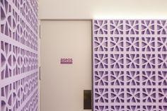 Heladería La Ibense. Revestimiento de paredes con celosía de hormigón pintada. Acceso a los aseos. Proyecto de interiorismo de AZ Diseño.
