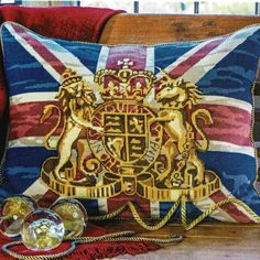 The United Kingdam Royal Coat of Arms in golds with a background of the Union Jack flag.