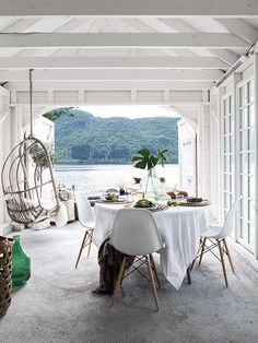 beautiful white covered terrace with a view over a lake dining table eames chairs hanging chair.