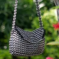 Shiny soda pop-tops sparkle like stars in the midnight sky in the original design of this shoulder bag. Neide Ambrosio designs this extraordinary bag featuring a zipper pocket in the lined interior. By recycling pop-tops, Ambrosio makes an affirmation for environmental responsibility. The bag closes with a magnetic button