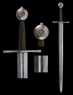 "A German Medieval Sword, circa 1350  The front of the pommel has an inset brass eagle (Reichsadler) and the back has a dragon. The fullered blade is inlaid with a cross potent of the German Order of the Knights.   Overall length: 113.5 cm (44.7""); Blade length: 88 cm (34.6"")  Located at Reichsstadtmuseum Rothenburg, German"