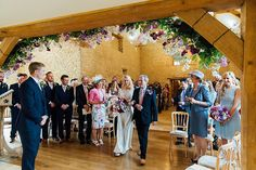 A Charlie Brear gownf for a colourful, flower-filled wedding at Kingscote Barn. Photography by Charlotte Bryer-Ash.