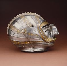 Close helmet with mask visor, ca. 1515 Attributed to Kolman Helmschmid (German, 1471–1532) Augsburg, Germany, steel, embossed, etched, and gilt. Helmets fitted with mask like visors were a popular German and Austrian fashion about 1510 to 1540. With their visors forged and embossed as humorous or grotesque human masks such helmets were often worn in tournaments held during the exuberant pre-Lenten (Shrovetide) festivals, celebrations somewhat akin to the modern Mardi Gras, Rogers Fund.