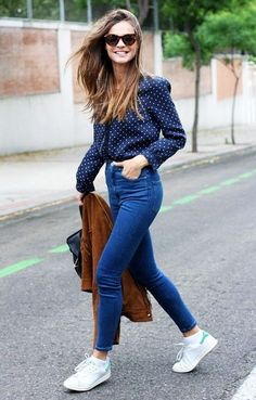 A polka-dot button-down is paired with skinny jeans, white sneakers, and a suede jacket