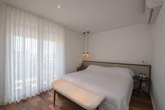 Com piso em madeira de demolição, uma das suítes do apartamento em Campinas (SP) tem decoração clara. Destaque para os pendentes (Lumini) ao lado da cama. O projeto de interiores tem assinatura da arquiteta Elaine Carvalho
