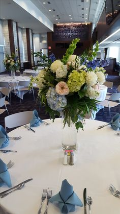 Wedding reception centerpiece by Kistner's Flowers, Manhattan KS  Elevated floral arrangement with blue hydrangea, green hydrangea, white football mums, garden roses