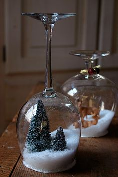 Dry snow globes made from wineglasses fitted with cardboard covers to which objects (trees, deer, snowman, etc.) have been glued. Cover cardboard in decorative paper and run a bead of glitter glue along rim. Use as candleholder or as plate stand. Cute and easy for tabletop party decor. Could redo with paper confetti and Easter eggs or sand and seashells. So versatile!