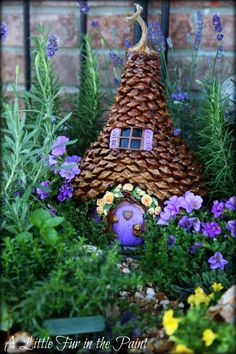 Pine cone Fairy garden with beautiful purple front lawn*****Follow our unique garden themed boards at www.pinterest.com/earthwormtec *****Follow us on www.facebook.com/earthwormtec for great organic gardening tips #fairygarden #fairy