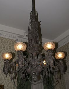 Victorian gothic gaslight chandelier looks ready for Halloween, dripping in black figures and garlands