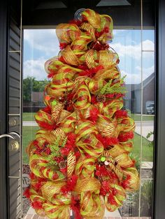 "Deco Mesh Christmas Tree Door Hanging  $125      This is a red tree form that measures about 40"" tall by 24"" wide. Then this has a red/lime green plaid deco mesh ribbon and gold mesh ribbon throughout the tree. Then this has beaded picks throughout the wreath and pine picks with berries as well. This is very beautiful in person and you can put lights behind it and the lights will show up on the other side. This is a half cone tree, so I can do the other have and make a whole cone tree that…"