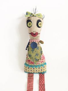 Lolalovita is a one of a kind art doll. She is created with variety of mismatched printed fabrics and trim. She has big, beautiful green eyes and red lips. She is stained and given a wash of acrylic paint to give her a grungy, aged appearance. She measures approx. 11 sitting. Maybe hung on wall.