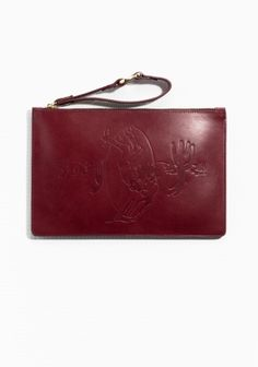 Embossed rodeo motif elevates the western spirit of this meticulously crafted wristlet clutch in rich burgundy leather. Fine stich detailing and gold-tone hardware elegantly finish the style.