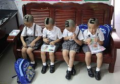 Six-year-old quadruplets, marked by their parents to help teachers identify them, wait outside their class in Shenzhen, China, Sept. 2012. GETTY IMAGES