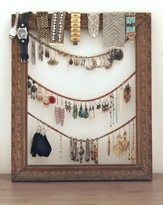 A decorative empty frame with chains loosely hung across - DIY jewelry holder and displayer