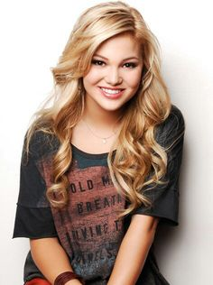 Olivia Holt acts on the show Kickin' It and starred in the movie Girl Vs. Monster. She's a Christian who often posts Bible verses on her social media accounts and sang Child of Faith at a County Fair. She is dating the Christian singer Luke Benward.