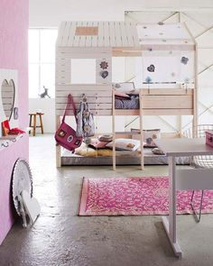 This indoor play house and bunk bed combo makes a great centerpiece for this hip pink and white girls' room.