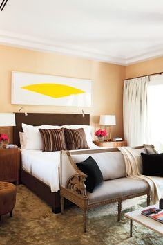 Neutral bedroom with vibrant artwork and brown pillows