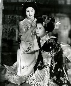"""Gion Bayashi (1953)    Michiyo Kogure as Geiko Miyoharu in the background and Ayako Wakao as Maiko Miyoei in the foreground, who is shown here, being dressed for her Misedashi (debut as a Maiko).    directed by Kenji Mizoguchi in 1953,  in the USA under the title """"A Geisha"""" in 1978."""