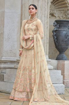 Beige Premium Net Wedding and Party Wear Anarkali Suit. The beige net top is beautifully weaved together with resham and zari embroidery with intricate sequins and stone work all over. The anarkali suit comes with a shantoon bottom Bridal Anarkali Suits, Bridal Lehenga Choli, Pakistani Wedding Dresses, Pakistani Bridal, Indian Dresses, Indian Outfits, Lehenga Kurta, Nikkah Dress, Lehenga Wedding