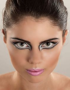 White around the eyes and wide eyeliner can make the eyes look much bigger from a distance. White around the upper lip also gives the lip a sharper crease. Visit http://ballroomguide.com/comp/hair_make_up.html for more hair and makeup info