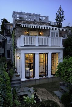 """""""Exterior of a traditional home at night - By Thorsen Construction - black and white striped awning - white washed brick - rooftop patio"""" oh, this is gorgeous"""