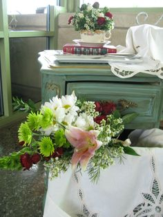 Cake table. Open drawer with loose bouquet. Teacup posy on book.
