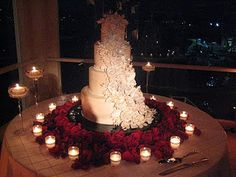 Gorgeous cake w/beautiful deep red roses on the table