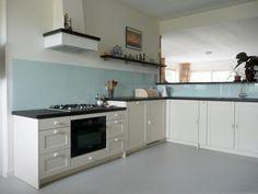 Landelijke witte keuken, donker werkblad, schouw en lichtblauwe glasplaat