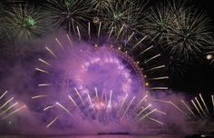 Fireworks explode around the London Eye wheel during New Year 2014 celebrations in central London