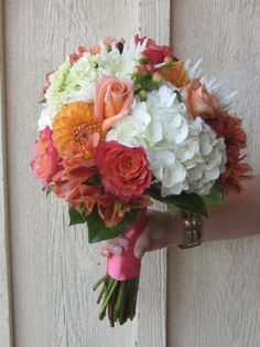 Passionate and fun this hand held bouquet features Free Spirit roses, orange dahlias, white hydrangea, and hypericum berries with a coral ribbon wrap.