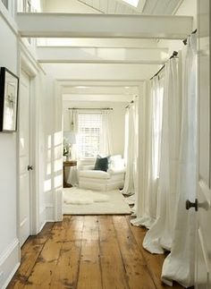 I love the contrast of the white walls, curtains, and furniture against the beautiful wood floors. The lighting is very sweet, too. Simple and beautiful.