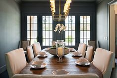 The deep, gray walls add an unexpected panache to the design. White upholstered chairs are the perfect accent.