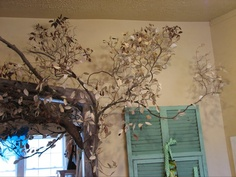 The tree branch at Honeysuckle Hollow in Hendersonville, NC. The leaves are punched out of book pages! Branches attached to the wall.