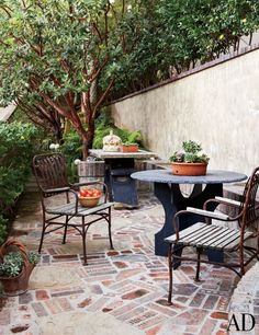 The outdoor breakfast area has antique stone tables and vintage Italian chairs | archdigest.com