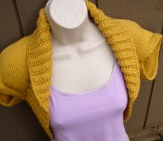 """The Mustard Yellow Knit Shrug will make a wonderful addition to any wardrobe, as a gift or for yourself. This Shrug is knit in a medium worsted weight yarn, so it is a little heavier than most of my shrugs. It has garter stitch arm holes that cap the top of your shoulders. This item features a 4"""" moss rib edging that creates a collar, which extends around the torso, giving a body hugging effect. Perhaps it would make a good cover up for a strapless party dress? Or layered over a lightweight…"""