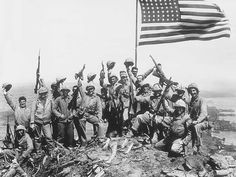 U.S. Marines of the 28th Regiment, fifth division, cheer and hold up their rifles after raising the ... - AP Photo/Joe Rosenthal