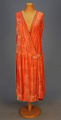 1920's. BEADED VELVET DRESS, Sleeveless rose pink having pink beaded flowerheads and crystal beaded abstract blocks, wrap front closing with a beaded medallion, slight gathers at the dropped waist, a narrow panel falls from left shoulder to below the hem.