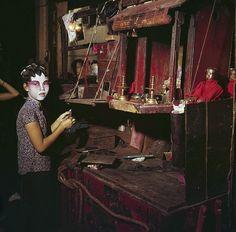 CHOLON 1961 - Une jeune fille, vêtue d'un chemisier imprimé bleu, se maquille à l'aide d'une spatule, les sourcils accentués par les traits au pinceau noir, un dégradé de rouge au rose allant des paupières aux joues sur un fond blanc appliqué à son visage. Ses cheveux sont en cours de préparation, maintenus par des papillotes en papier aluminium; prise de vue dans une loge au décor dépouillé: un miroir, deux bougeoirs et un bouddha. (Photo by Jack Garofalo/Paris Match via Getty Images)