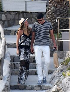 Holiday vibes: The 36-year-old supermodel was summer chic in a black and white jumpsuit and cream fedora