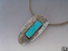 PENDANT STERLING SILVER AND BEZEL SET AMAZONITE CABOCHON. ROLLING MILL TEXTURED WITH A HAND ETCHED BRASS PLATE ,SINCLASTIC SHAPE.